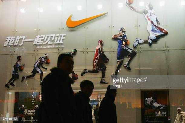 People pass by the Nike shop on December 26 2007 in Beijing China The Beijing Olympic Games will bring enormous commercial opportunity to Beijing