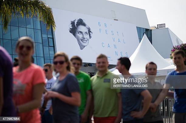 People pass by the official poster of the 68th Cannes Film Festival showing the Swedish actress Ingrid Bergman on the Festivals palace facade in...