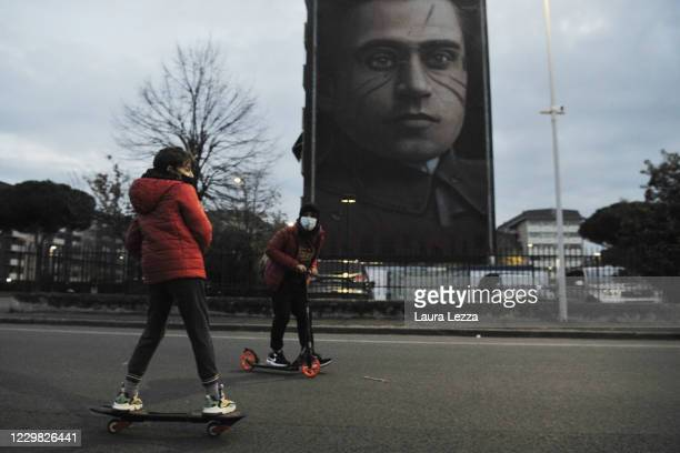 People pass by while street artist Jorit is painting a mural dedicated to the politician and philosopher Antonio Gramsci and paying a tribute to the...