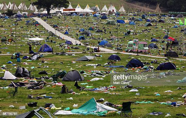 People pass discarded tents and rubbish on the start of the big clearup of the Glastonbury Festival site at Worthy Farm Pilton on June 29 2009 near...