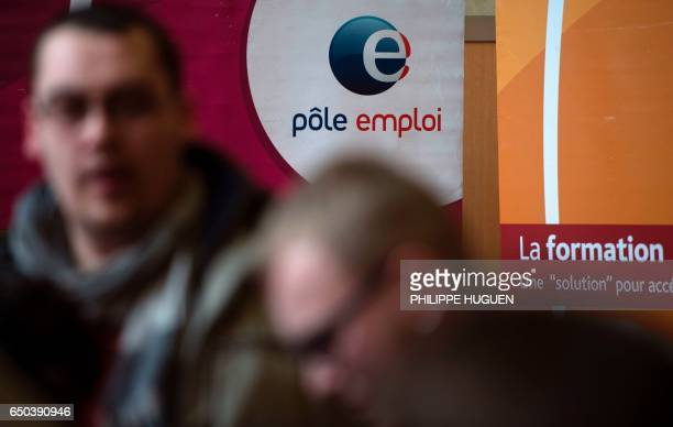 People pass in front of an Pole Emploi panel on March 8 2017 in Dunkirk the French economy has created close to 190000 net positions in 2016 an...