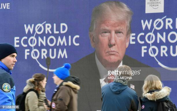 People pass in front of big screen during the speech of US President Donald Trump on January 26 2018 at the Davos Congress Centre the venue of the...