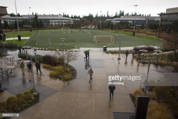 People pass in front of employees playing soccer on a field at the Microsoft Corp main campus in Redmond Washington US on Tuesday Dec 19 2017 In the...