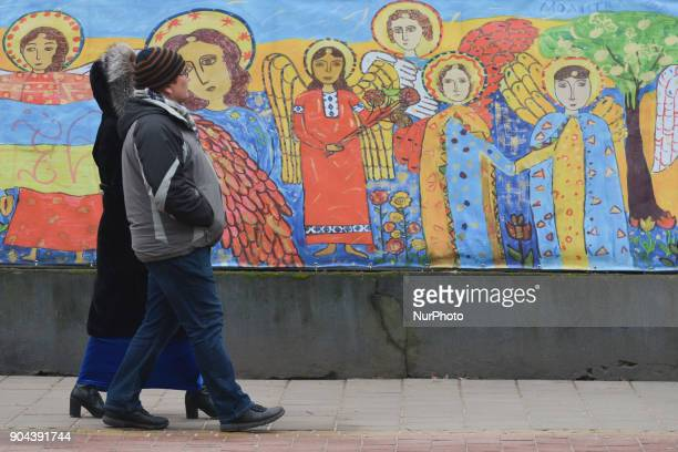 People pass in front of the Art Work created by young children during a competition 'Golden Easel' featuring a magnificent 100meter canvas around the...