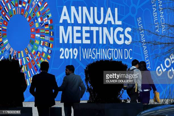 People pass in front of the IMF building during the IMF and World Bank Fall Meetings on October 15, 2019 in Washington, DC. - The world economy is...