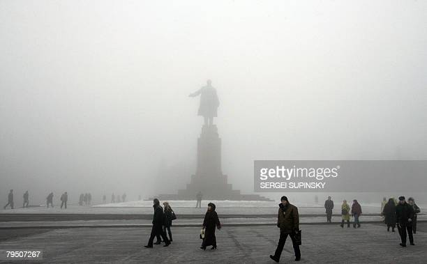 People pass Lenin's monument in the centre of the Ukrainian city of Kharkiv during a very foggy day on February 4 2008 AFP PHOTO/ SERGEI SUPINSKY