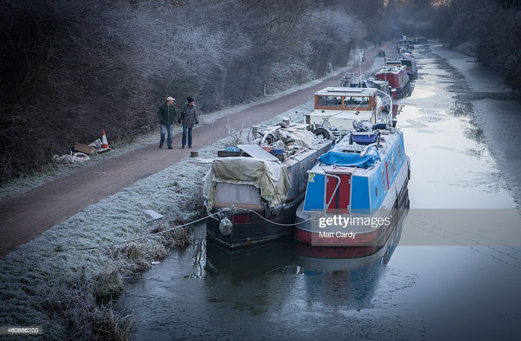 People pass narrowboats moored on the canal near Bathampton on December 29, 2014 in Bath and North East Somerset, England. According to the Met Office Britain experienced the coldest night of the year overnight, with some areas being even colder than Alaska and the Antarctica and as forecasters believe it could get even colder tonight, a Met Office cold weather alert for northern England and the Midlands has warned of health risks for vulnerable people.
