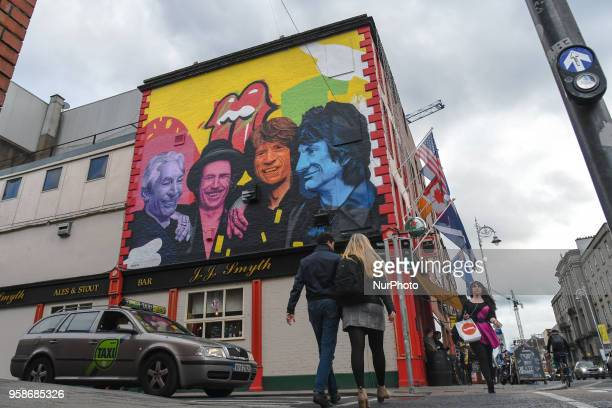 People pass near a new mural by Subset Dublin paying tribute to The Rolling Stones a legendary English rock band has appeared in Dublin's city centre...