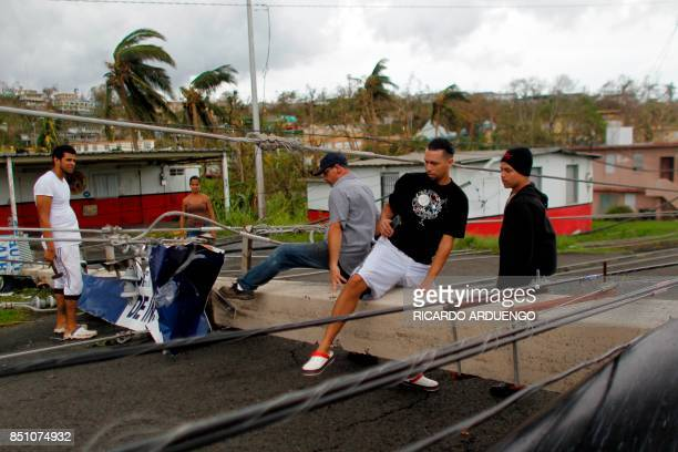 People pass over a downed power line concrete post in the aftermath of Hurricane Maria in Luquillo Puerto Rico Thursday September 21 2017 Puerto Rico...