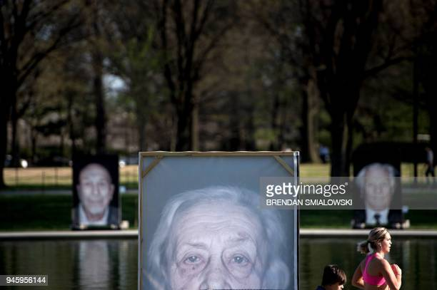 People pass portraits of Holocaust survivors during the Lest We Forget exhibition along the Reflecting Pool at the National Mall on Holocaust...