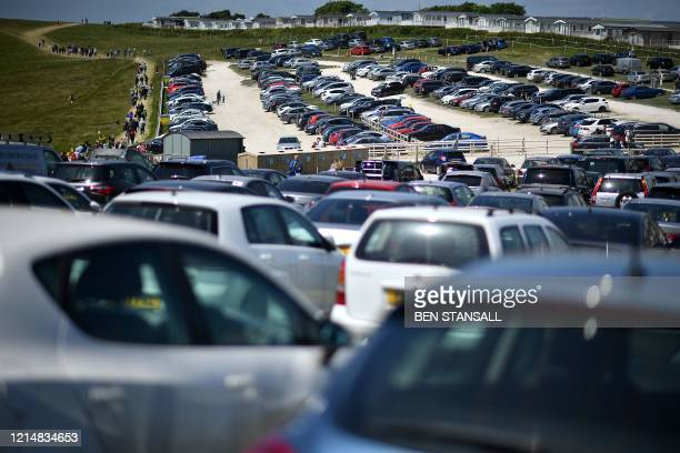 People pass rows of parked vehicles in the car park as they walk on a leading to the popular tourist spot Durdle Door near West Lulworth on the south...