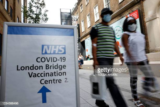 People pass signs indicating the entrance to the London Bridge Vaccination Centre in London on August 9, 2021. - After updated guidance from British...