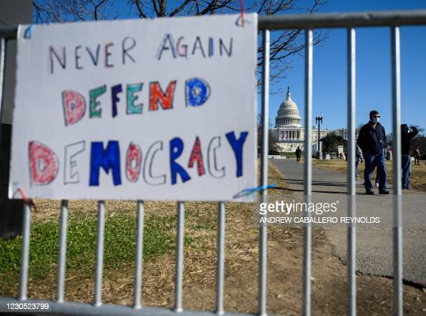 People pass signs of support near the US Capital in Washington, DC on January 10, 2021. - Donald Trump faced fresh calls Sunday from some members of...