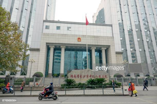 People pass the Changsha City Intermediate People's Court in Hunan Province on November 21 where former lawyer Jiang Tianyong was sentenced to two...