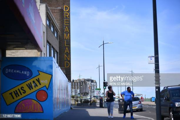 People pass the Dreamland amusement park in Margate south east England on May 16 following an easing of lockdown rules in England during the novel...