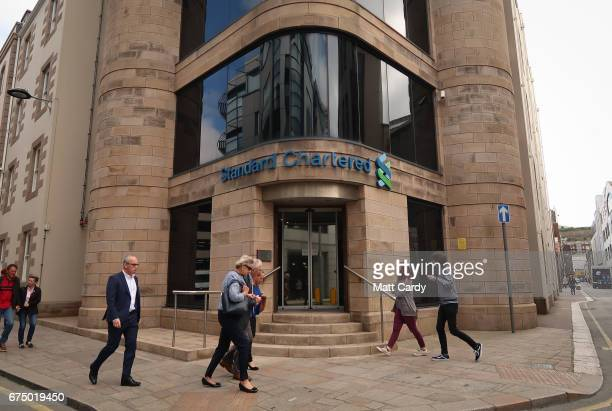 People pass the offices of Standard Chartered in St Helier on April 12 2017 in St Helier Jersey Jersey which is not a member of the European Union is...