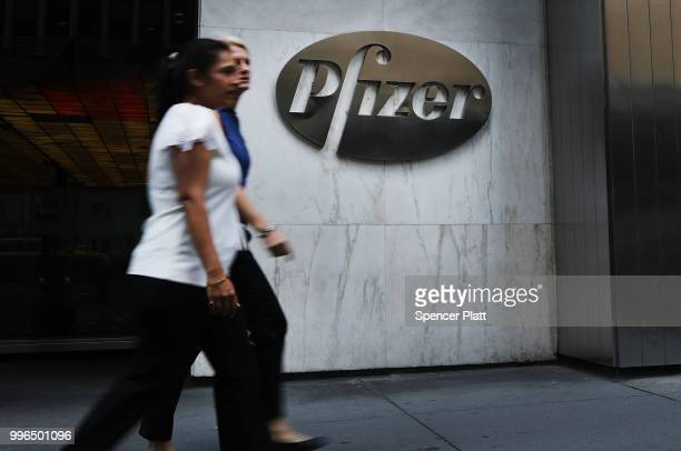 People pass the Pfizer headquarters in Manhattan on July 11 2018 in New York City A day after President Donald Trump pressured the pharmaceutical...