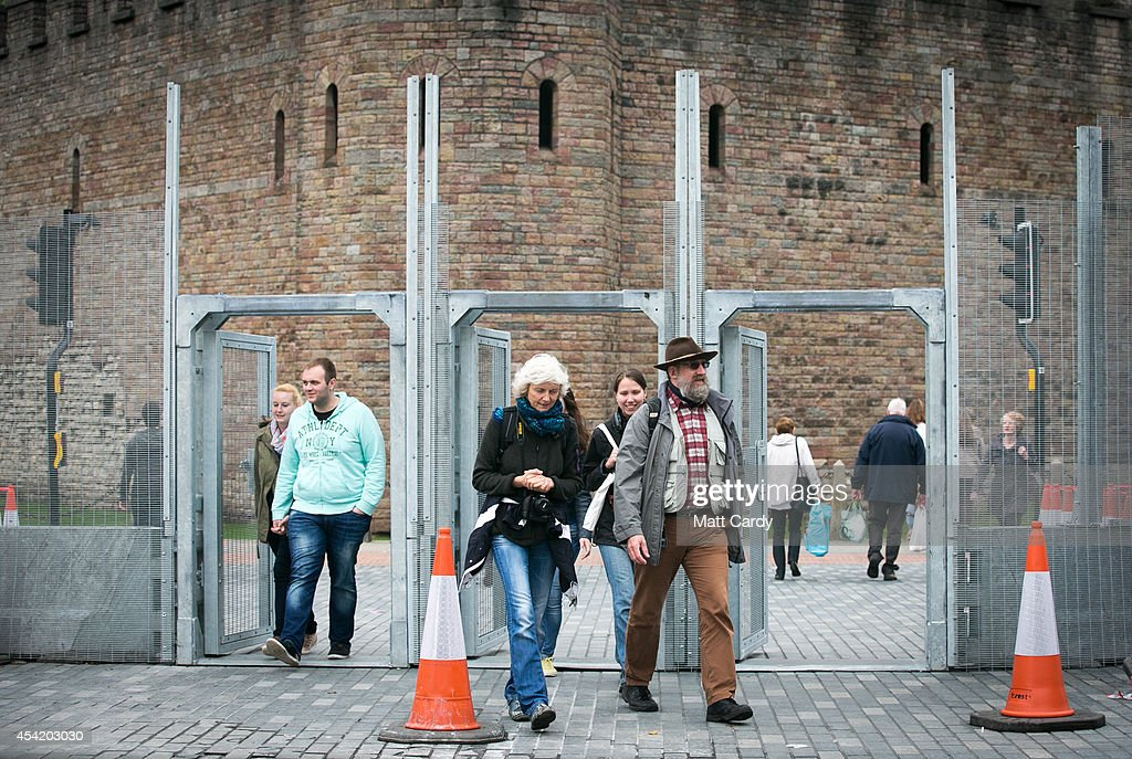 People pass through a pedestrian gate that has been fitted in the security fence that has been erected in front of Cardiff Castle ahead of the NATO summit that is being held in South Wales next week on August 26, 2014 in Cardiff, Wales. The barriers have been erected in the Welsh capital as a security measure as preparations for the international conference continue at the Celtic Manor Resort in Newport.