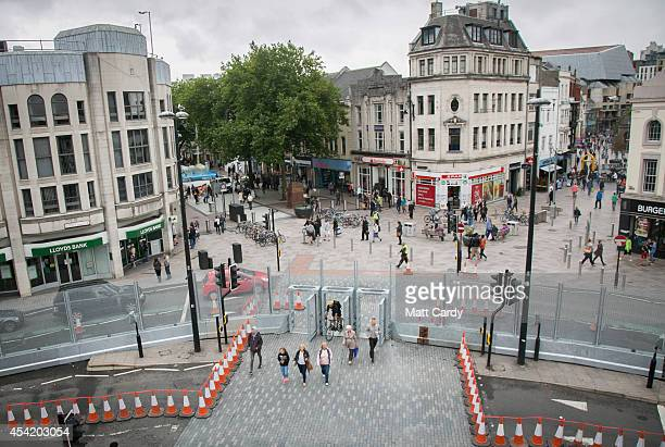 People pass through a pedestrian gate that has been fitted in the security fence that has been erected in front of Cardiff Castle ahead of the NATO...