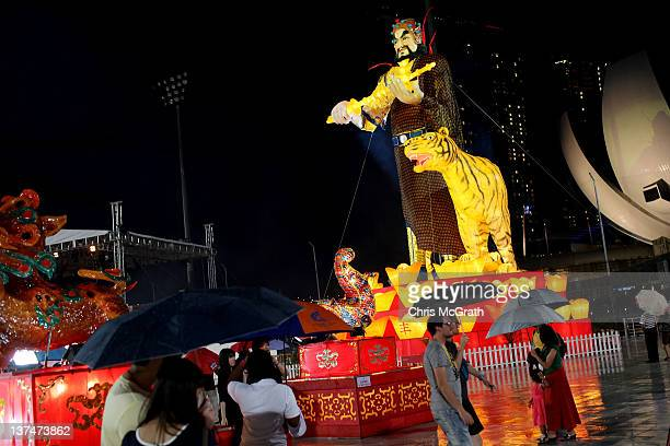 People pass under a large lantern of the Martial God of Wealth warrior Zhao Gong Ming during the public opening of the 2012 River Hongbao Festival on...