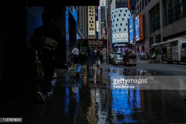People pass walk by the Nasdaq building as the screen shows the logo of the video-conferencing software company Zoom after the opening bell ceremony...