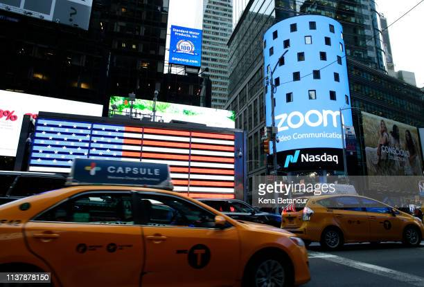 People pass walk by the Nasdaq building as the screen shows the logo of the videoconferencing software company Zoom after the opening bell ceremony...