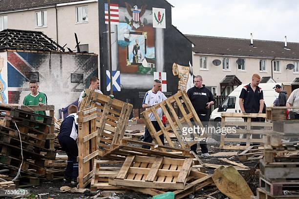 People pass wooden crates as they build a bonfire on the Shankill Road on July 11 in Belfast Northern Ireland The bonfires which are seen by the...