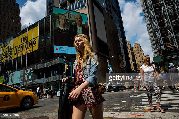 People pass works of art displayed on digital billboards in Times Square August 4 2014 in New York City A total of 58 classic and contemporary works...