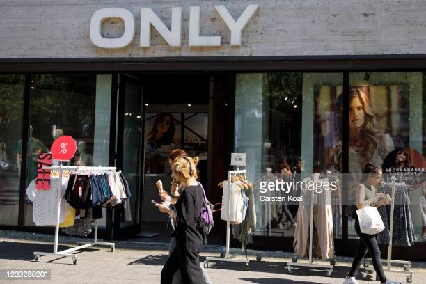 People passing a clothing store on the second day that people are no longer required to show a negative Covid test result to enter non-essential...