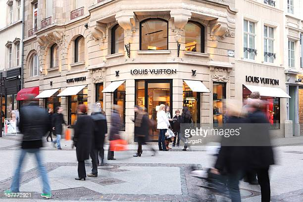 People Passing by a Louis Vuitton Store