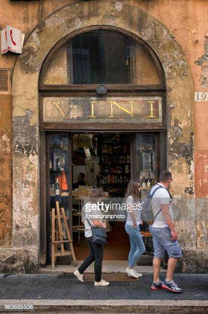 people passing by a wine shop entry. - emreturanphoto stock pictures, royalty-free photos & images