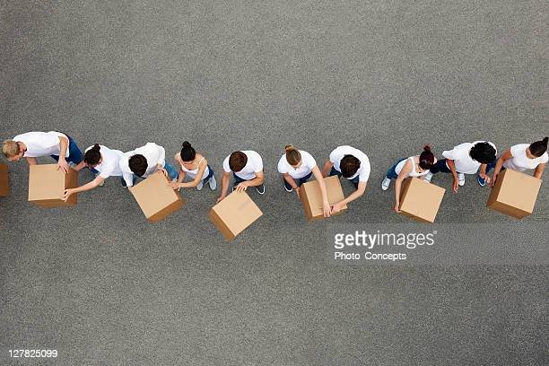 people passing cardboard boxes - giving stock photos and pictures