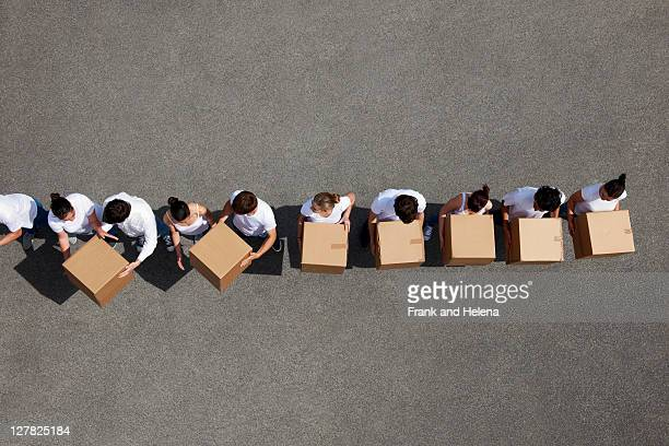 People passing cardboard boxes