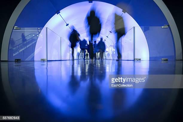 People passing LED illuminated tunnel