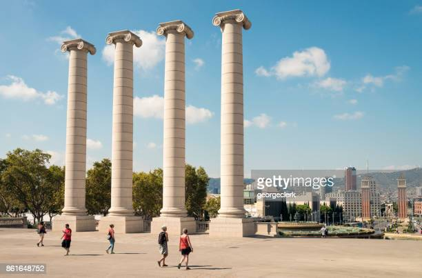 People passing monumental columns in Barcelona