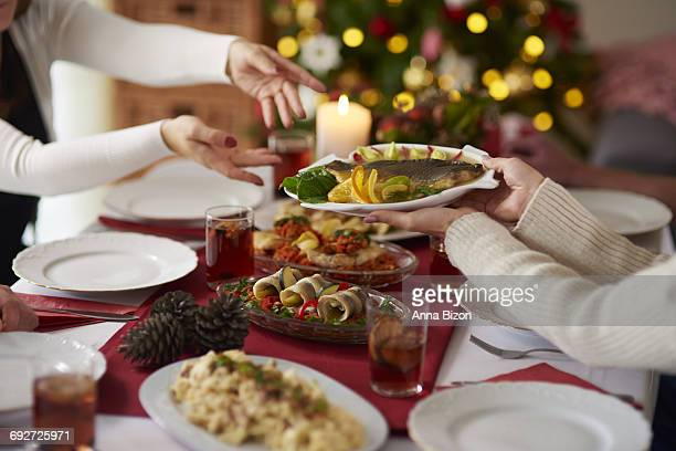people passing plate with christmas carp. debica, poland - carp stock photos and pictures