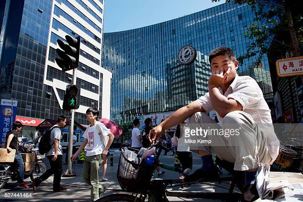 People passing the shopping malls and offices in Zhongguancun or Zhong Guan Cun a technology hub in Haidian District Beijing China It is situated in...