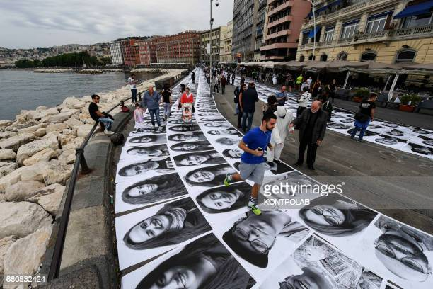 People paste 3000 portraits of Neapolitan on the ground as part of the installation 'Inside Out' by French artist JR on the seafront in Naples
