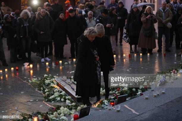 People pause at a memorial to victims following the memorial's inauguration at the site of the 2016 Christmas market terror attack at...
