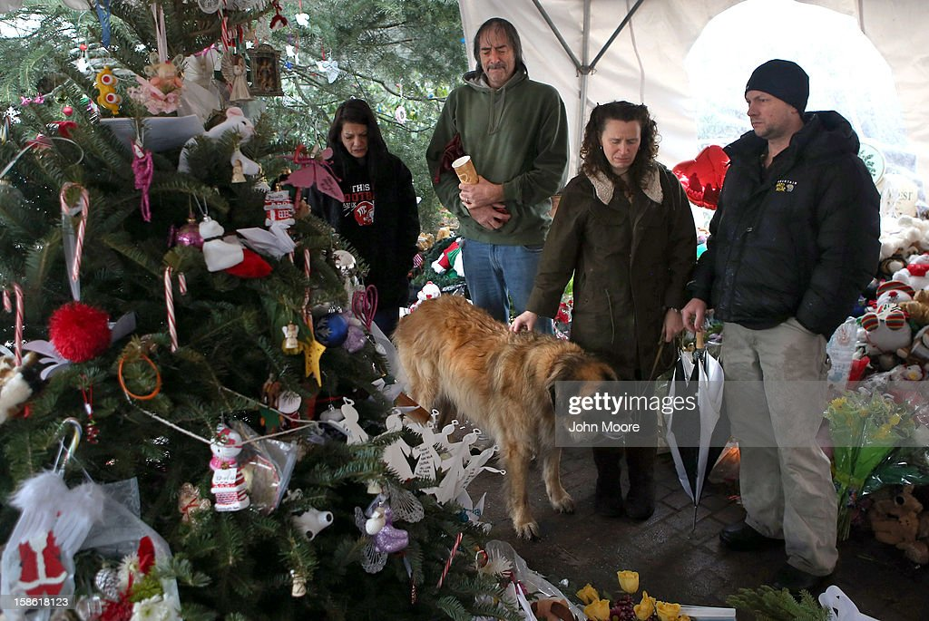 People pause at a streetside memorial during a moment of silence on December 21, 2012 in Newtown, Connecticut. Church bells rang out at 9:30 EST to mark the one-week anniversary of the Sandy Hook Elementary School massacre.