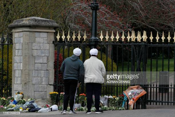 People pause at floral tributes laid at the Cambridge Gate at Windsor Castle, in Windsor, west of London, on April 9 following the announcement of...