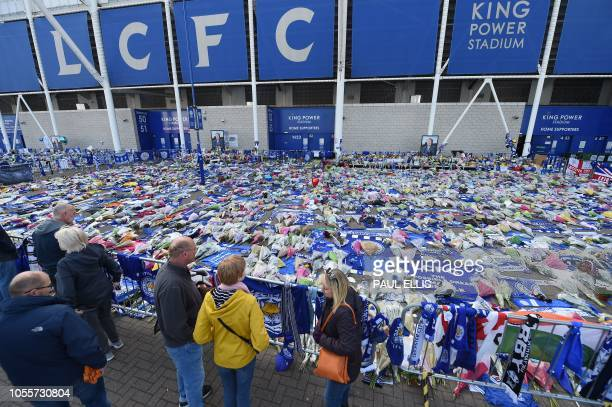 People pause at the tributes gathered outside Leicester City Football Club's King Power Stadium in Leicester eastern England on October 31 2018 in...
