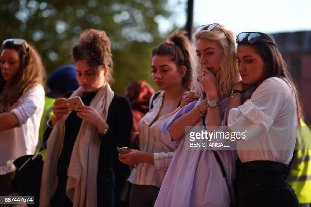 TOPSHOT People pause in front of candles set up in front of floral tributes in Albert Square in Manchester northwest England on May 23 in solidarity...