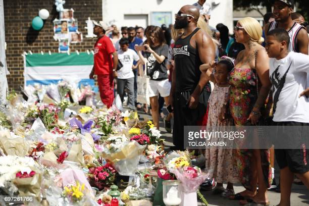 People pause in front of memorial tributes to the victims and the missing from the Grenfell Tower block fire close to the scene in North Kensington...