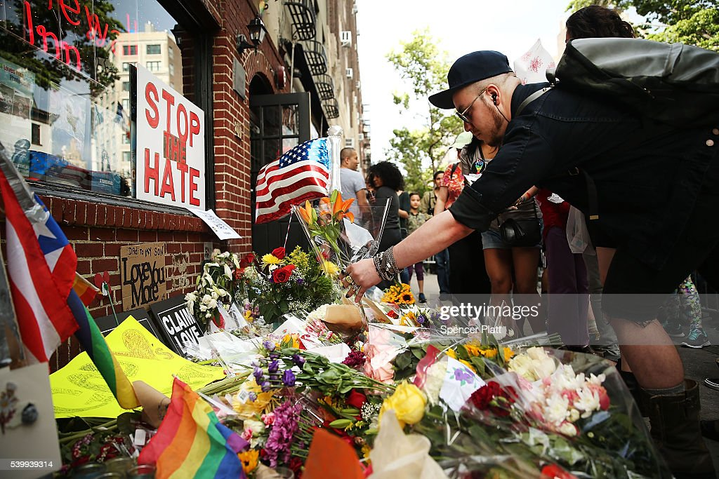 People pause in front of the iconic New York City gay and lesbian bar The Stonewall Inn to lay flowers and grieve for those killed in Orlando on June 13, 2016 in New York City. An American-born man who had recently pledged allegiance to ISIS killed 50 people early Sunday at a gay nightclub in Orlando, Florida. The massacre is the deadliest mass shooting in United States history.