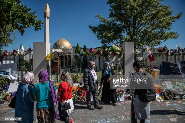 People pause next to flowers and tributes outside Al Noor mosque on March 24 2019 in Christchurch New Zealand 50 people were killed and dozens were...