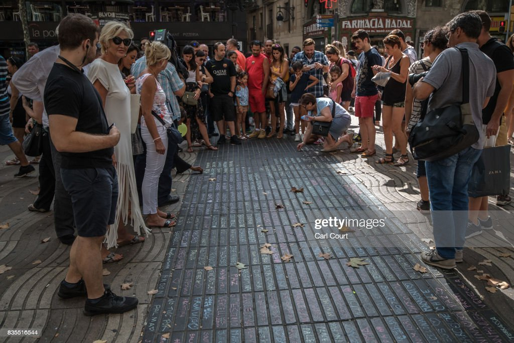 People pause next to messages written on the ground on Las Ramblas near the scene of Thursday's terrorist attack, on August 19, 2017 in Barcelona, Spain. A nationwide manhunt continues for Younes Abouyaaqoub, now named by Spanish media as the suspected driver in an attack that left thirteen people dead and dozens injured when a van was driven at crowds in the popular Las Ramblas area of Barcelona on Thursday.