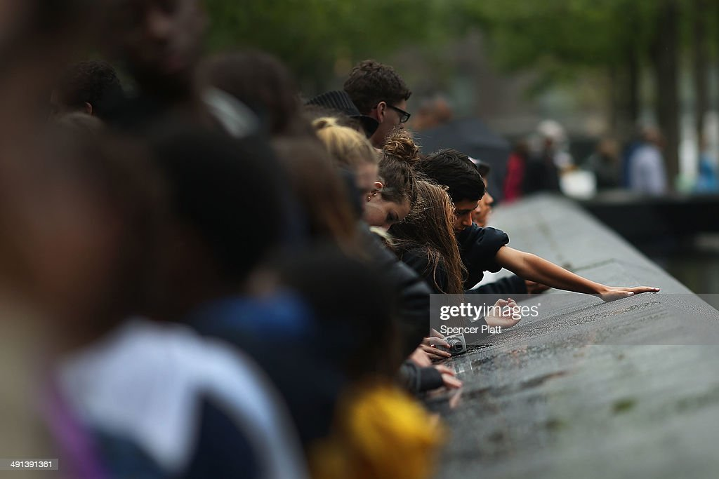 People pause pauses at the names engraved along the South reflecting pool at the Ground Zero memorial site after authorities opened the plaza to the public free of charge on May 16, 2014 in New York City. Prior to today, visitors had to wait in line to enter a barricaded area which includes the newly dedicated National September 11 Memorial Museum. Together with the museum, Ground Zero has become one of the top tourist attractions in the nation with tens of thousands of visitors expected yearly.