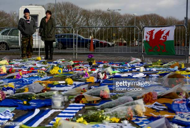 People pause to look at the Cardiff City scarves and jerseys flowers messages and other tributes to the football club's new signing Emiliano Sala...