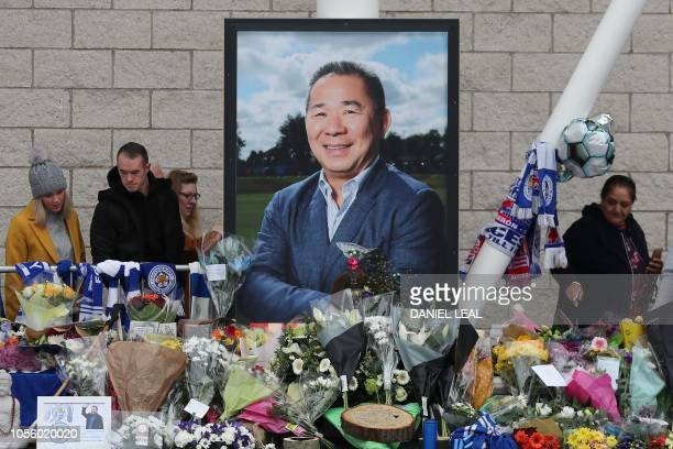 People pause to view and pay their respects at the tributes layed outside Leicester City Football Club's King Power Stadium in Leicester eastern...
